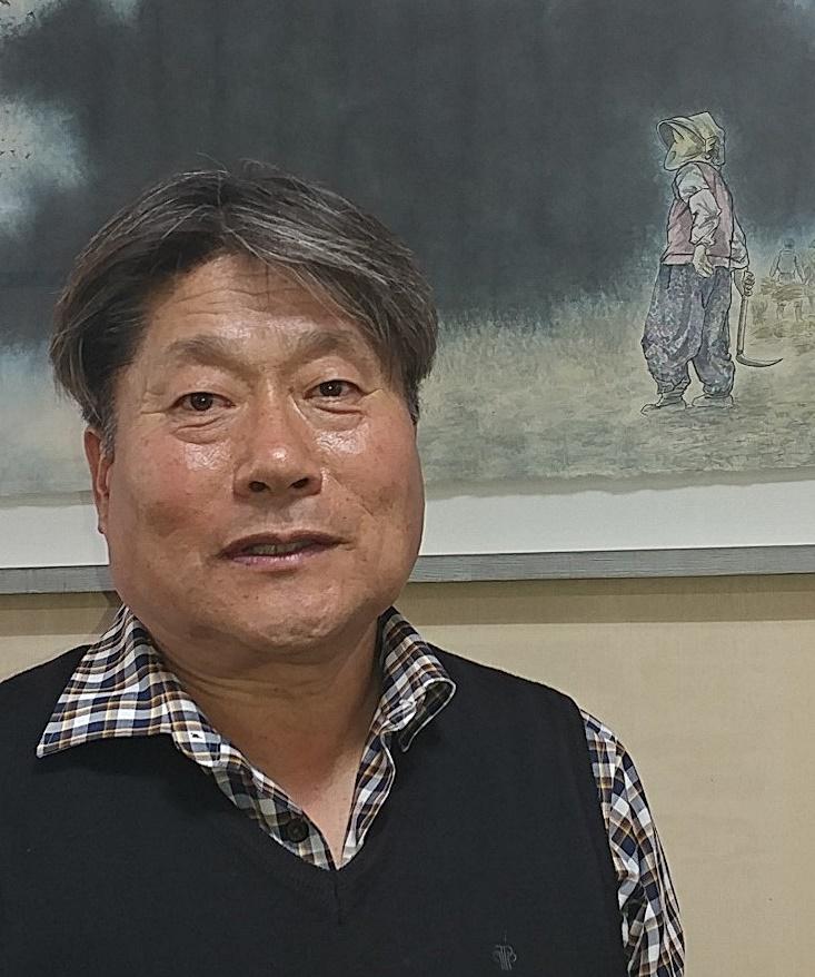 김영호 민중당충남도당 위원장. 그의 뒤로 가을 걷이를 하는 낫을 든 한 농민이 들판을 내다보는 그림이 걸려 있다.