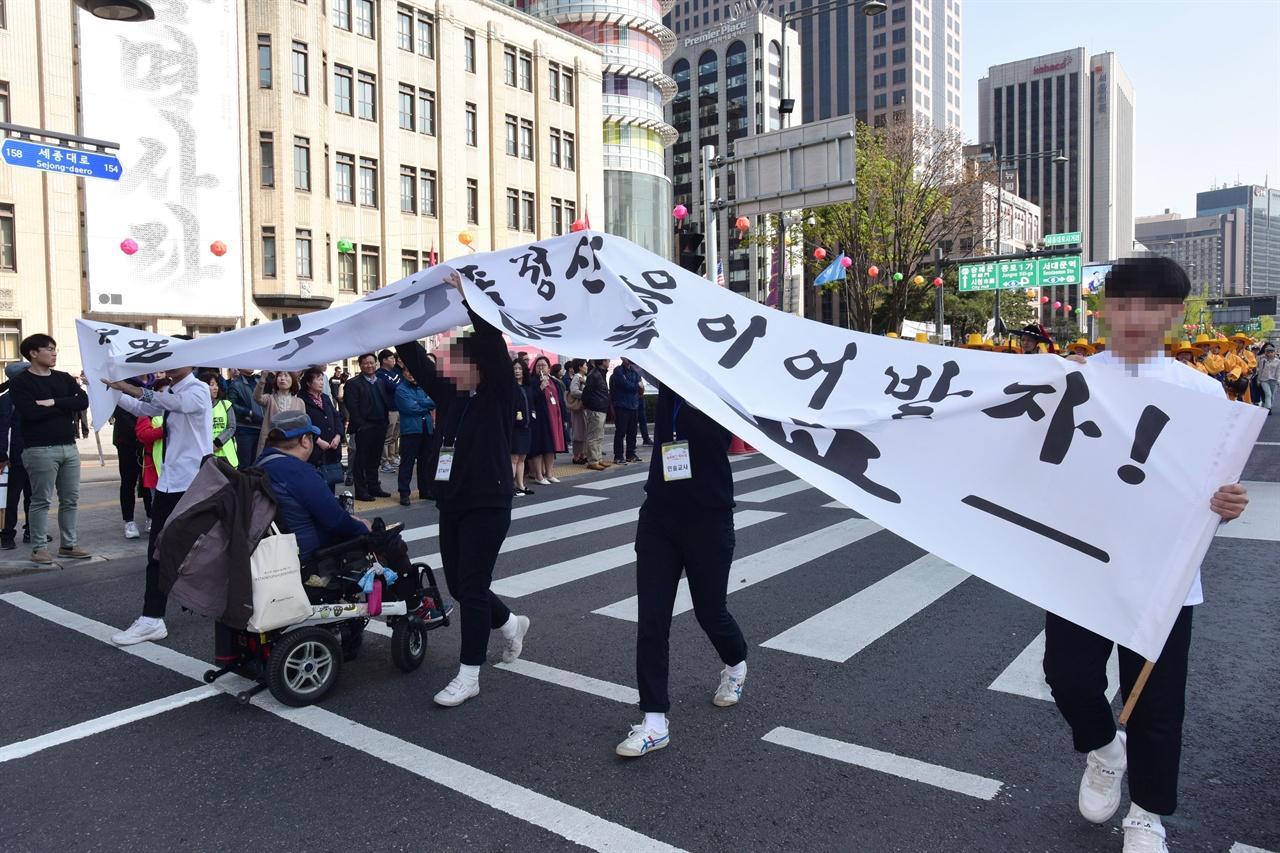 """19일 오후?'420 장애인 차별 철폐의날 행진' 참가자들이 서울 세종로 세종대로 사거리를 점거한채 '장애등급제 폐지""""를 요구하며 농성을 벌이자  '419혁명 대행진'을 벌이던 참가자들이 펼쳤던 현수막을 높이 들어 행진을 하고있다. 2019.4.19"""