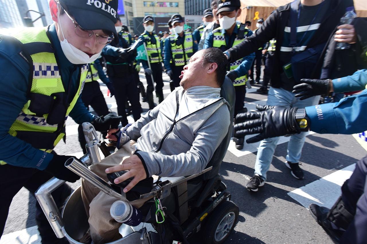 """19일 오후?'420 장애인 차별 철폐의날 행진' 참가자들이 서울 세종로 세종대로 사거리를 점거한채 '장애등급제 폐지""""를 요구하며 농성을 벌이자 경찰들이 인도쪽으로 이동시키고 있다. 2019.4.19"""