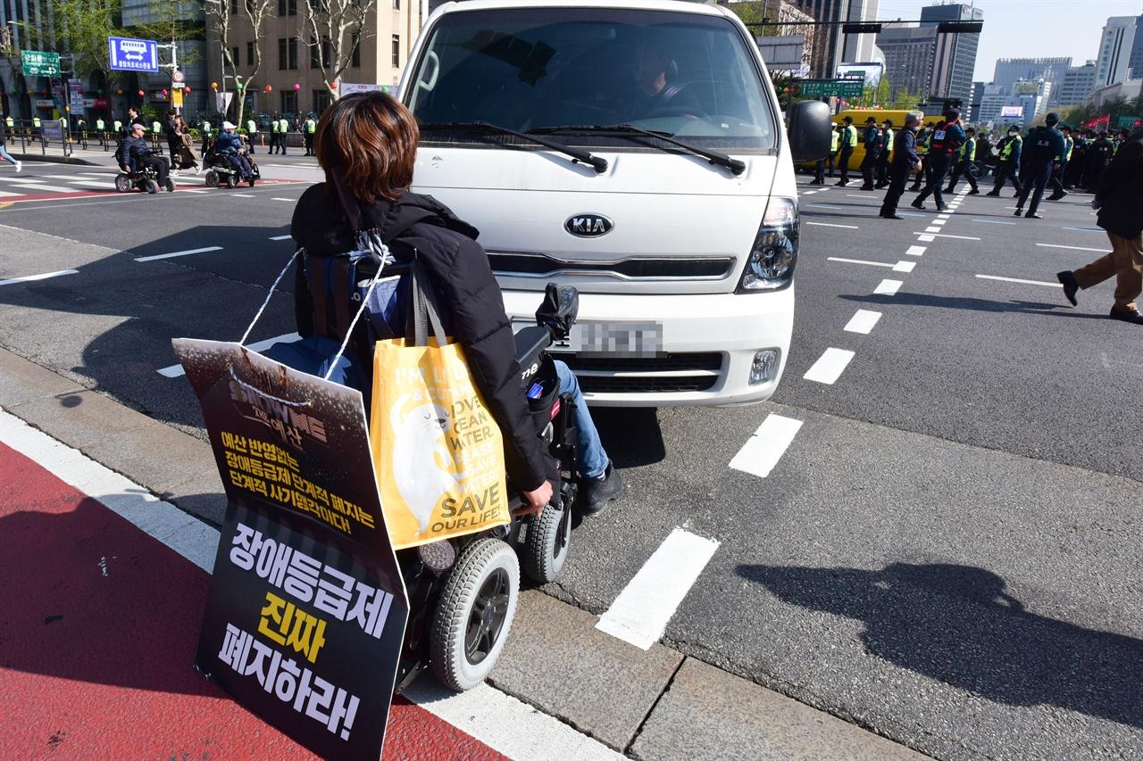 """19일 오후?'420 장애인 차별 철폐의날 행진' 참가자들이 서울 세종로 세종대로 사거리를 점거한채 '장애등급제 폐지""""를 요구하며 농성을 벌이고 있는 가운데 한 참가자가 차량의 막고 있다. 2019.4.19"""
