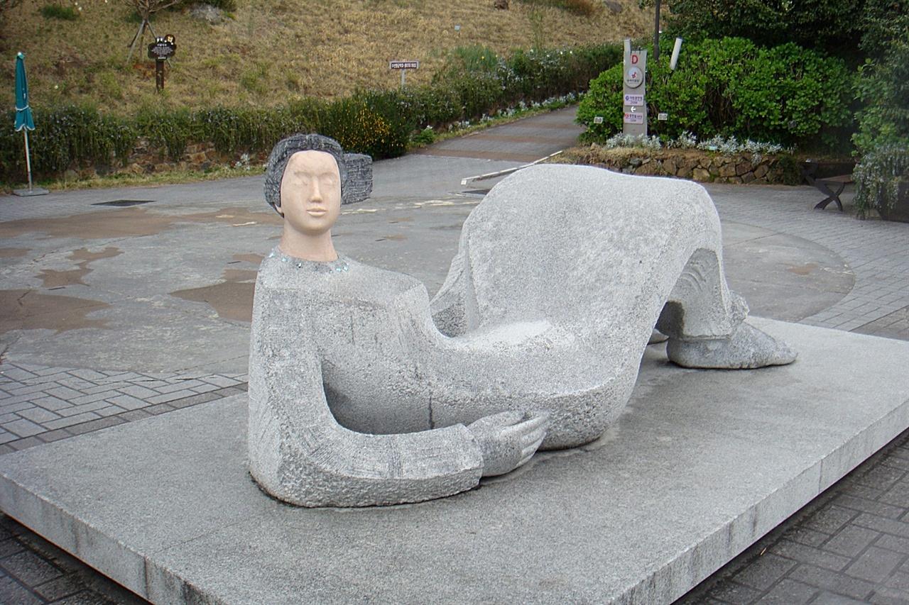 """장사도앞 멀리 지평선에 보이는 """"미인도""""를 형상화 한 누워있는 여인 조각상 모습"""