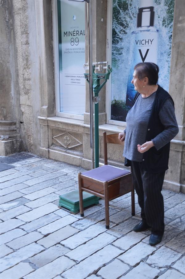몸무게를 재는 할머니. 사람 몸무게를 측정하는 데에 저울을 사용하고 있다.