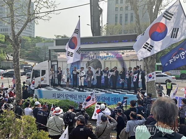 홍문종 자유한국당 의원이 24일 오후 서울중앙지검 앞에서 진행된 대한애국당 집회에 참석해 박근혜 전 대통령의 석방을 요구했다. 연단 가운데 회색 양복을 입은 인물이 홍 의원이다.