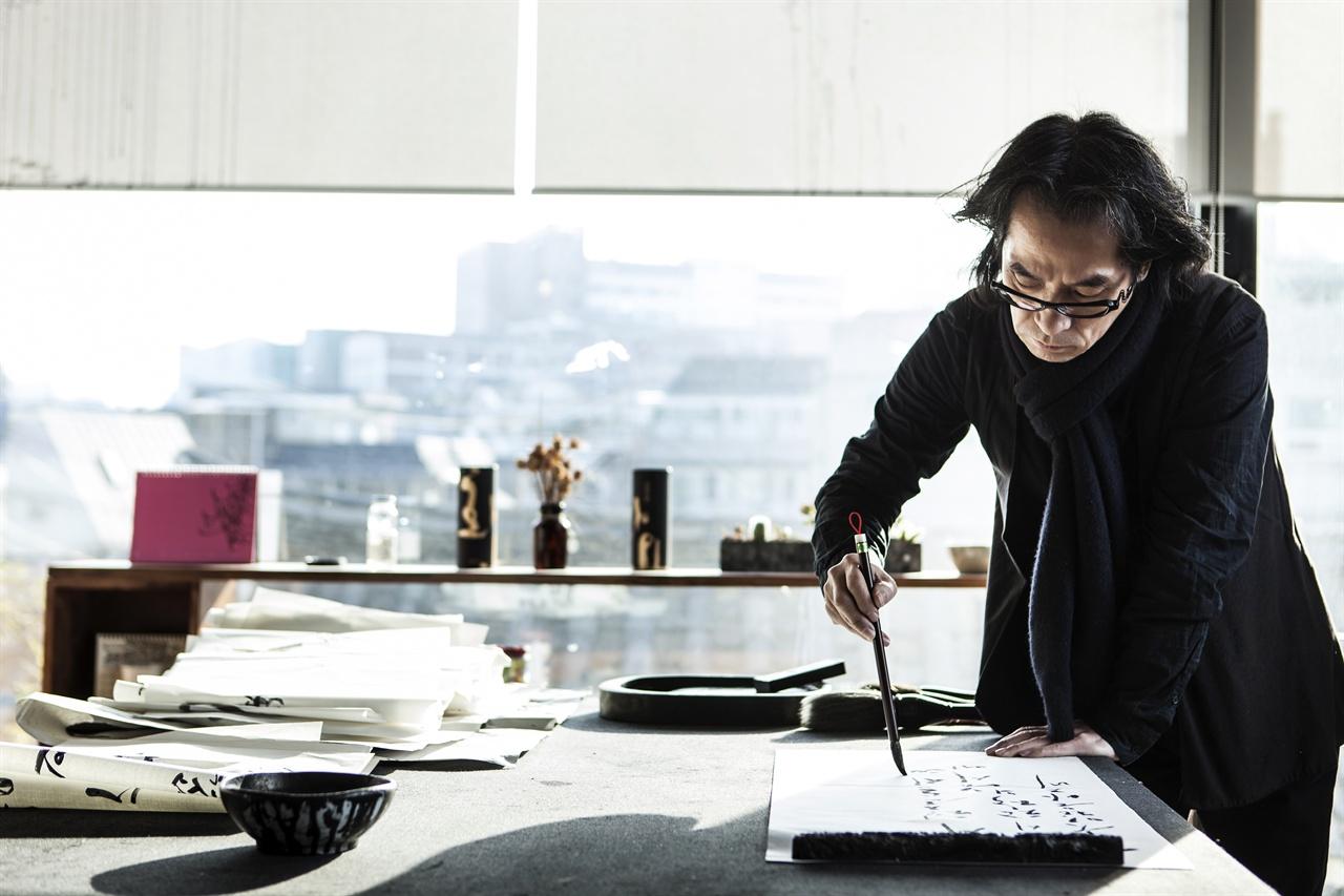 작업실에서 글씨를 써내려가는 강병인 멋글씨예술가