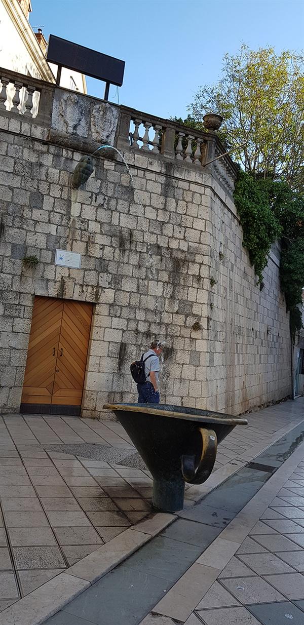 피르야 분수. 건물벽에서 나온 물이 반원 모양을 그리며 거리의 잔 속으로 떨어진다.