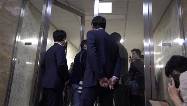회의장에 들어가는 출입구 양쪽을 봉쇄한 자유한국당 보좌진들과 들어가려는 기자 사이에 실랑이를 벌이는 모습