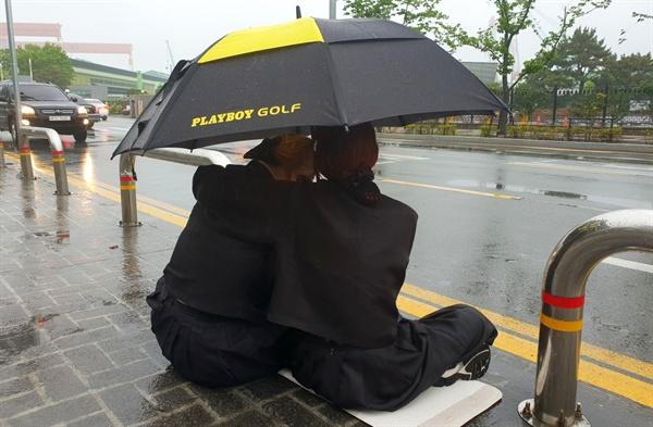 삼성중공업 사내 화장실에서 쓰러져 뇌출혈로 사망한 ㄱ(49)씨의 유족들이 비가 오는 속에 거리에서 시위를 하고 있다.