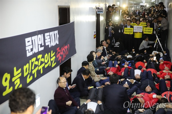 드러누운 자유한국당, '방해마!' 피켓 든 정의당 29일 오후 선거제도 개혁 패스트트랙 지정을 위한 정치개혁특별위원회(정개특위) 전체회의가 열릴것으로 예상되는 서울 여의도 국회 행안위 회의실 앞에서 자유한국당 의원들이 패스트트랙 저지를 위해 점거한 후 바닥에 누워 구호를 외치자, 정의당 의원들이 방해말라는 피켓을 들고 서 있다.