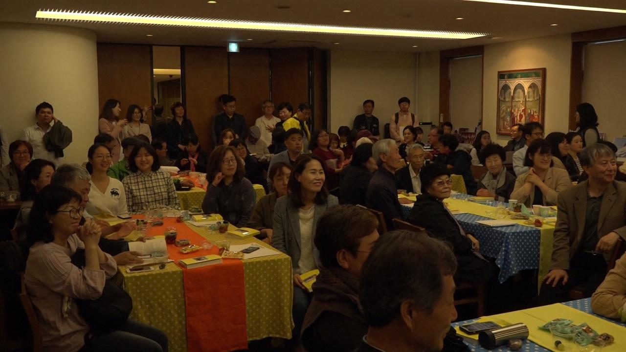 출판기념회 참가자들이 공연을 흐뭇하게 바라보며 미소짓고 있다