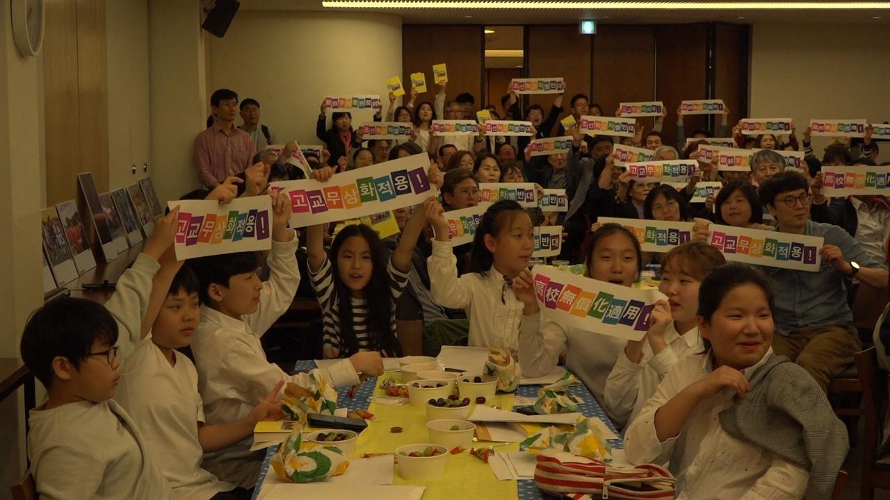 우리말과 일본어로 '고교무상화적용'이 적힌 구호를 든 참가자들