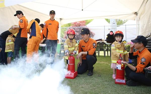 '서산 어린이 가족 한마당 축제'에 참가한 어린이들이 소방관들과 함께 직접 소화기를 다루는 체험을 하고 있다.