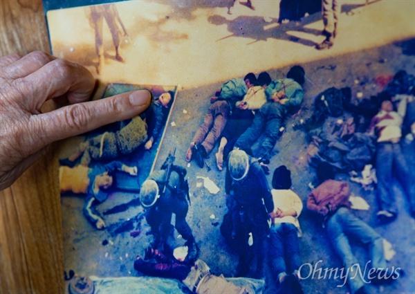 시신 속 아들 모습 가리키는 김길자씨 1980년 5월 27일 계엄군에 의해 전남도청에서 사망한 '고등학생 시민군' 고 문재학(당시 16세, 광주상고 1)씨 어머니 김길자(80)씨가 시신들 사진 속에서 아들의 모습을 손가락으로 가리키고 있다.