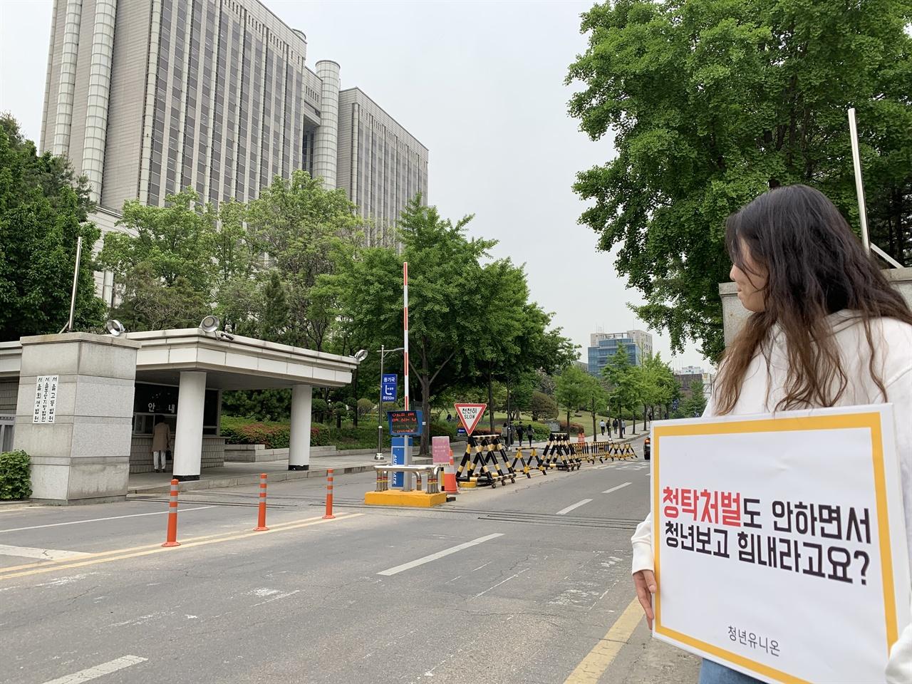 """채용 청탁자 처벌을 촉구하는 피캣 시위 2019년 5월 13일, 권성동 결심 재판 날 시민사회 활동가들이 """"채용비리 청탁자 처벌도 안하며, 청년보고 힘내라고요?""""라는 피켓 문구를 들고 법원 앞에 서있다"""