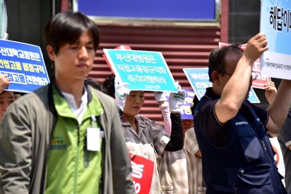"""부산대병원에서 일하는 노동자가 """"직접고용 정규직화 즉각 이행하라""""라고 적힌 손팻말을 들고 기자회견에 참석했다."""