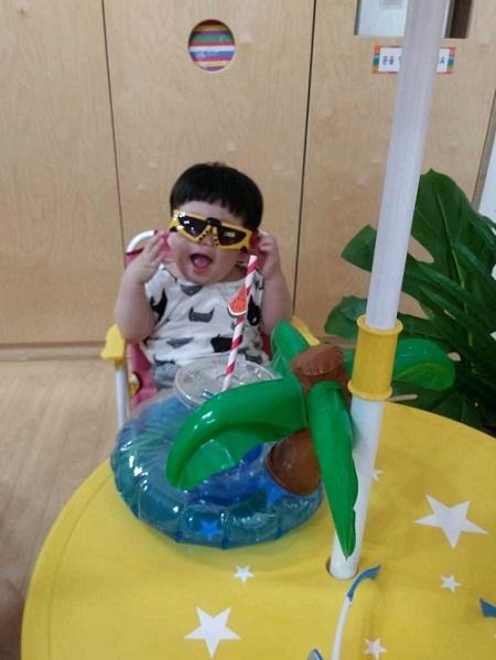 장난감도서관에 마련된 파라솔 의자에 앉아 선글라스를 끼고 즐거워하는 아이.