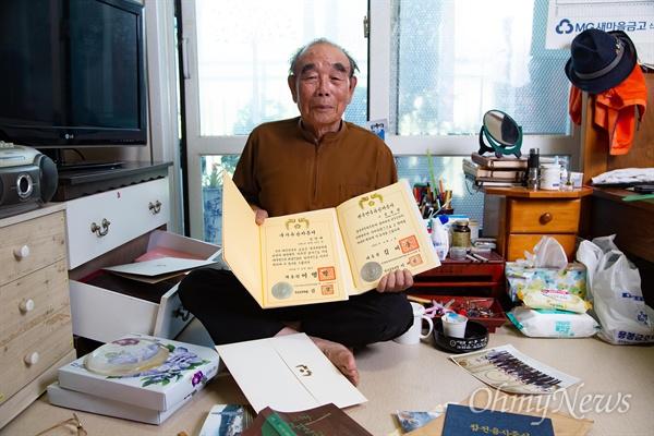 김영배씨가 본인의 6.25참전 '국가유공자증서'와 5.18민주화운동 당시 사망한 아들 김종철씨의 '광주민주유공자증서'를 들고 있다.
