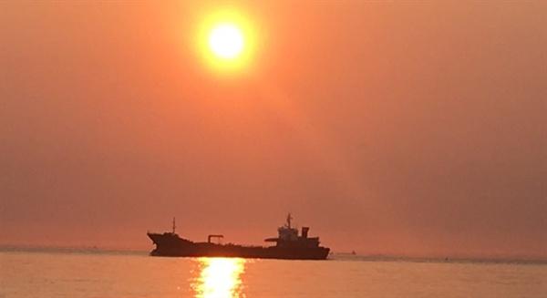 일몰 직전에 한 척의 배가 바다에 비친 태양 빛을 가로질러 지나가고 있는 모습은 환상상적 이었다