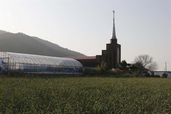 기동마을의 마늘밭과 어우러진 교회. 한낮의 마을풍경이 적막하다.