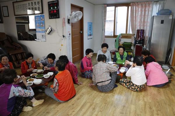 텃골경로당 풍경. 마을의 할머니들이 한데 모여 앉아서 저녁식사를 하고 있다.