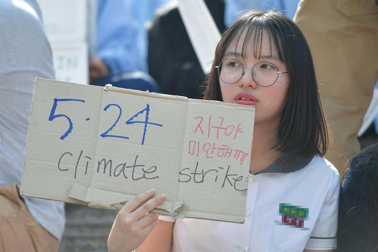 """24일 오후 서울 종로구 세종문화회관 중앙계단에서 열린 '524청소년기후변화 해결 촉구 공동행동'에 참여한 한 학생이 """"지구야 미안해""""라고 써진 손팻말을 들고있다. 2019.05.24"""