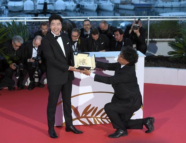 영화 <기생충>의 봉준호 감독과 송강호가 황금종려상 수상 후 포토콜 행사에서 포즈를 취하고 있다.