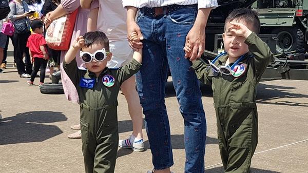 비행기 조종사 복장을 한 아이들이 아빠의 손을 잡고 걷고 있다.