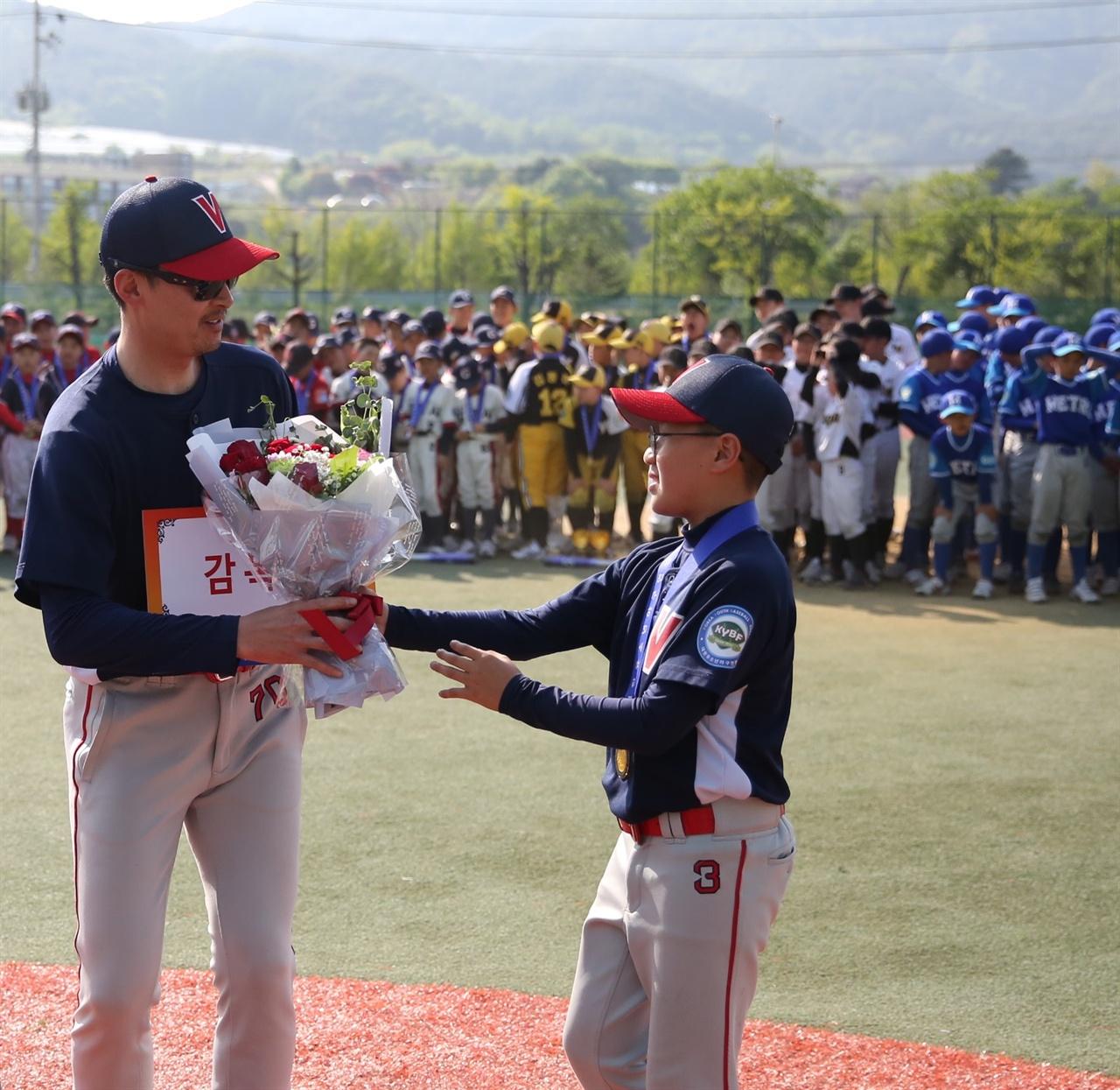 은평구VIP유소년야구단의 김성국 감독이 양구 전국유소년야구대회에서 감독상을 받으며 선수에게 꽃다발을 받고 있다.