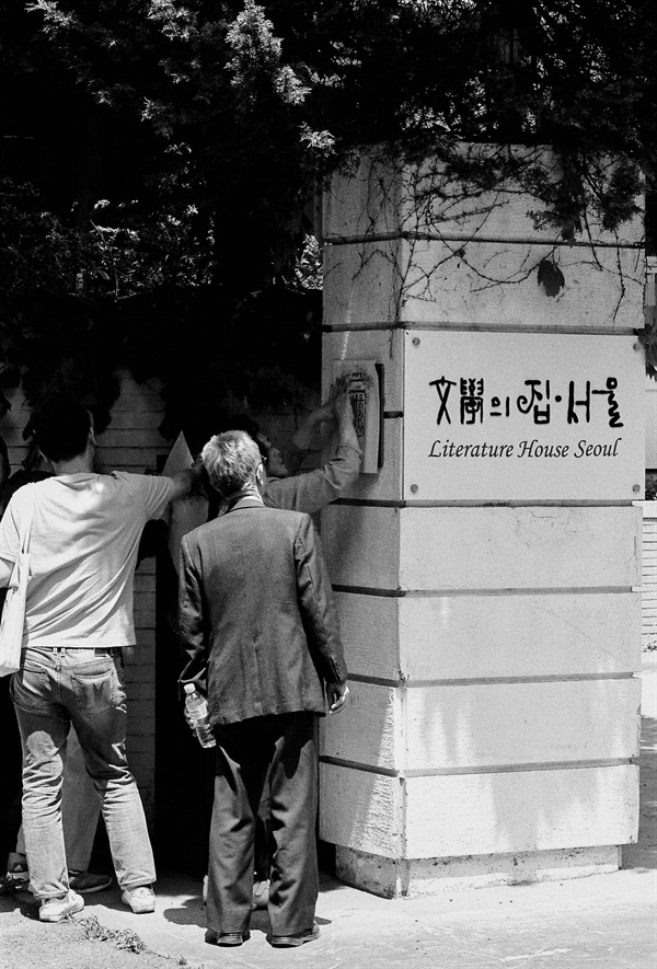 공관 알림판을 탁본하는 고문피해자들