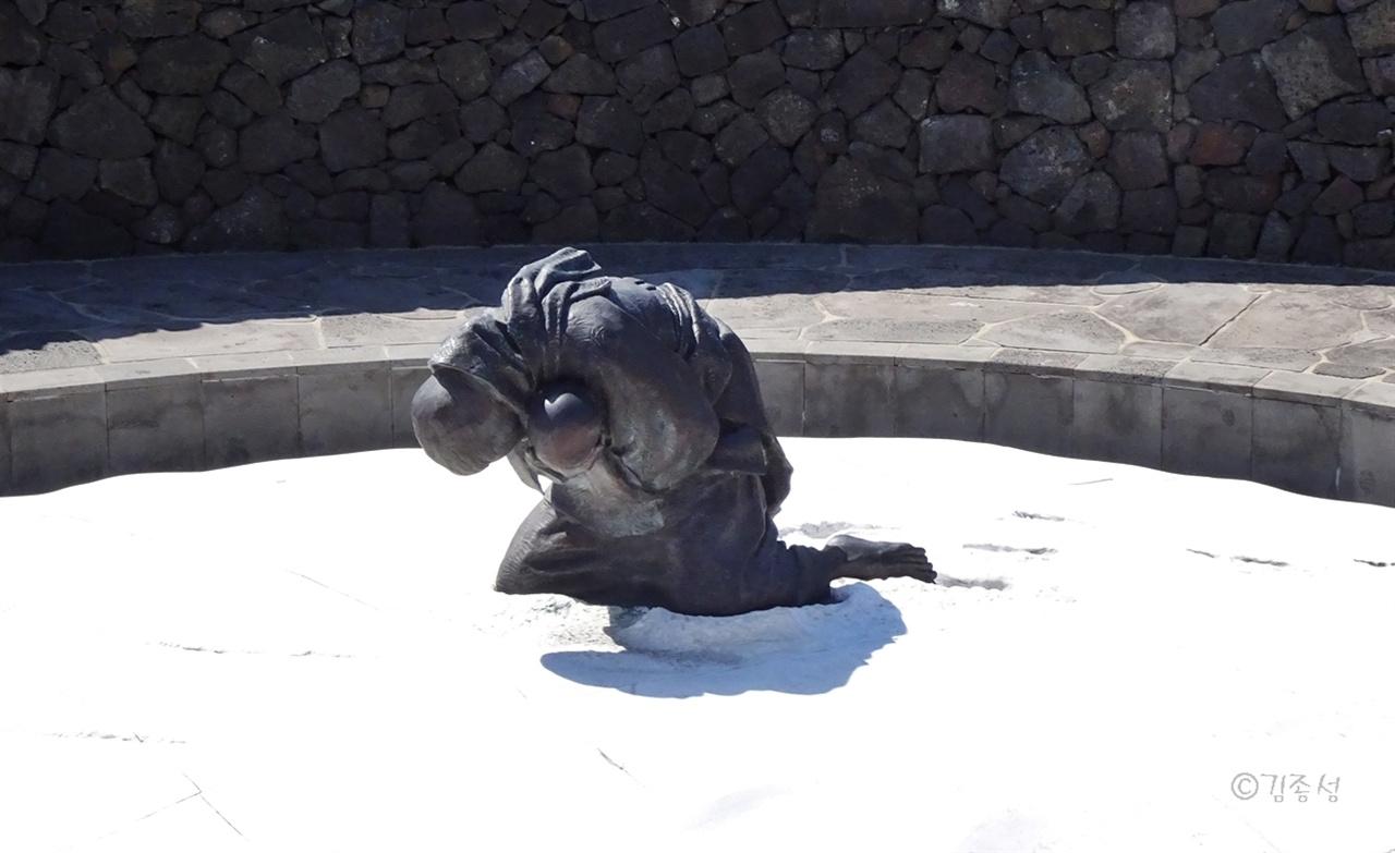 한 엄마가 아기를 품에 앉은 채 무릎을 꿇고 있는 모습의 조형물.