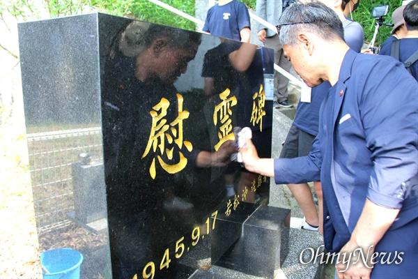 일본 기타큐슈시 오카마쓰의 '오다야마 묘지' 구석에 있는 '조선인조난자위령비'를 박광수 통일촌 대표가 딲고 있다.