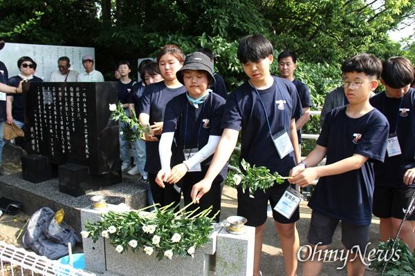 일본 기타큐슈시 오카마쓰의 '오다야마 묘지' 구석에 있는 '조선인조난자위령비'를 찾은 통일촌 회원들이 헌화를 하고 있다.