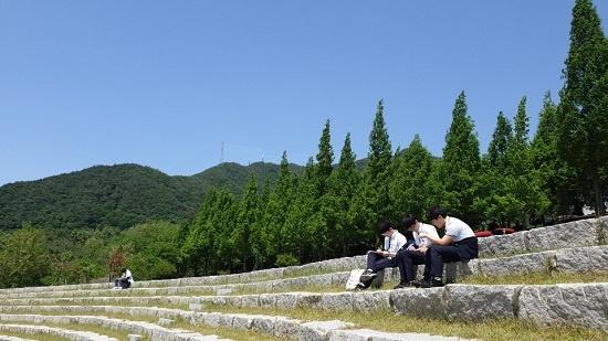 민송 백일장에 참가한 학생들이 삼삼오오 세명대 캠퍼스에 앉아 글을 쓰고 있다. ⓒ 이자영