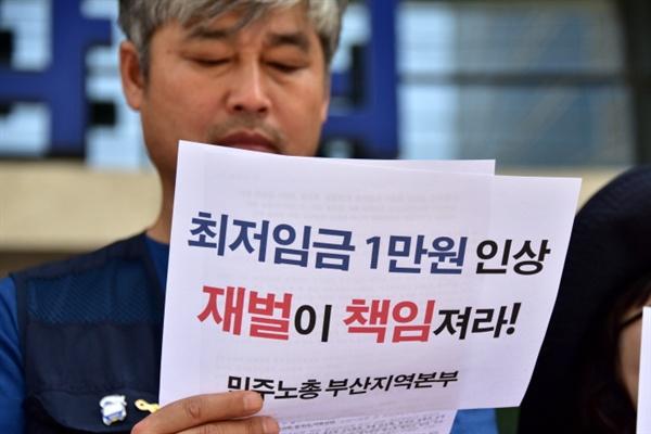 """""""최저임금 1만원 인상 재벌이 책임져라"""" 손팻말을 들고 있는 참가자"""