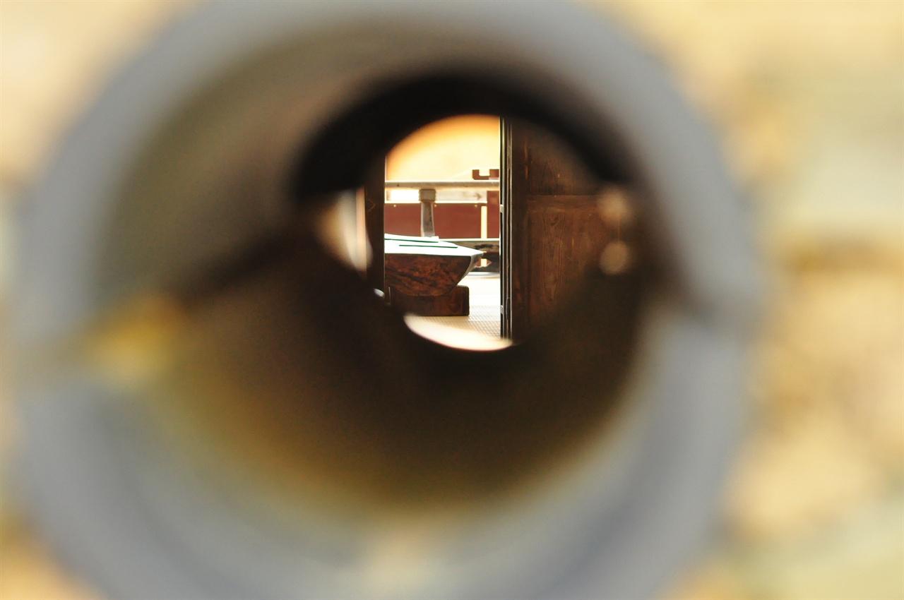 내외담에는 세 개의 구명이 나있다. 구멍으로 사랑채의 마루에 놓인 탁자가 보인다.