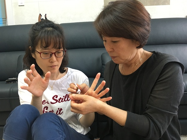 딸 한혜경씨의 손에 연고를 발라주는 엄마 김시녀씨의 모습.