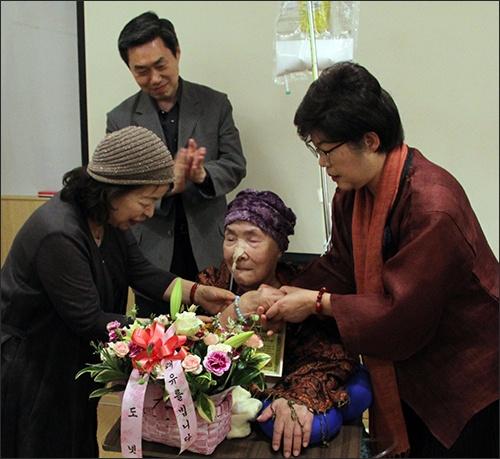 함께한 회원이 선물로 가져온 팔찌를 오희옥 지사 손목에 끼워드리고 있다.