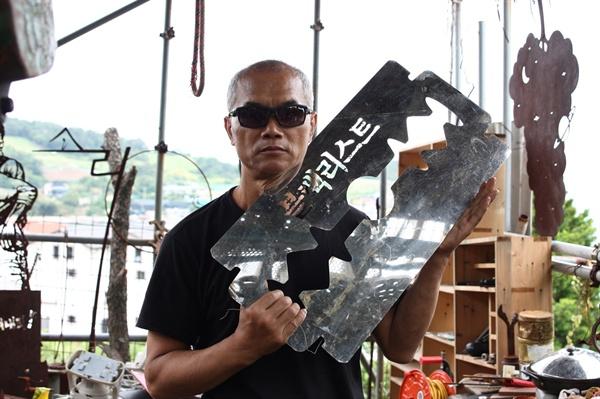 문화예술계 블랙리스트로 핍박받은 것을 표현한 작품을 들어보이는 최병수 작가. 블랙리스트는 살아있는 사람에게 면도칼을 목에다 들이댄 격이다