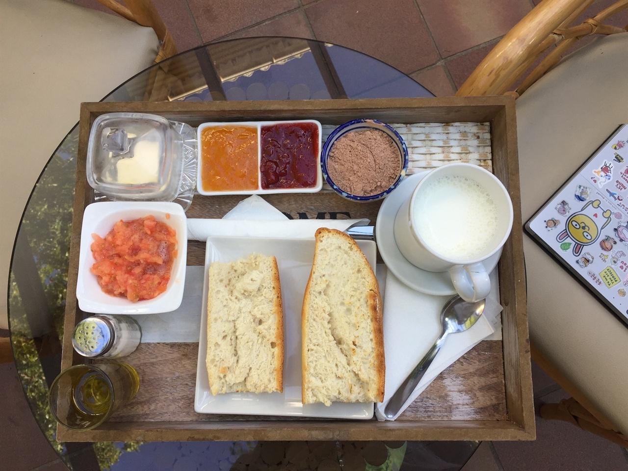 스페인식 아침식사입니다.  (제일 윗줄 왼쪽부터 시계방향으로 보면) 버터, 살구쨈, 딸기쨈, 초코파우더, 데운 우유, 구운 빵 & 토마토 간 것과 올리브 오일입니다. 이걸 골고루 빵에 올려서 먹는 것이, 전통적인 아침식사예요!