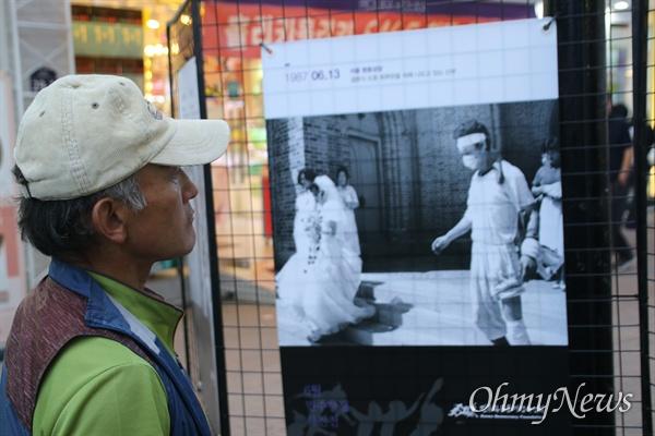 10일 오후 대구백화점 앞에서 열린 6.10항쟁 32주년 기념행사에 전시된 당시 사진들을 한 시민이 바라보고 있다.