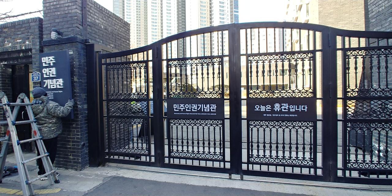 경찰간판이 있던 곳에 민주인권기념관 간판으로 교체하는 모습