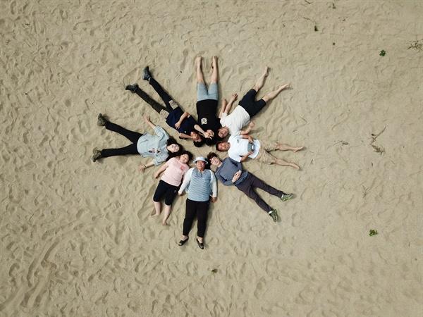 금강 창벽 앞에서 1박 2일 소풍을 마치고 모래톱에 누워 기념 사진을 찍는 사람들.