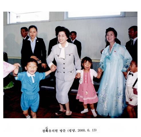 이희호 여사 생애사진 100선 2000년 평양 방문 이틀째 이희호 여사가 창광유치원을 방문해 아이들과 손을 잡고 춤을 췄다.