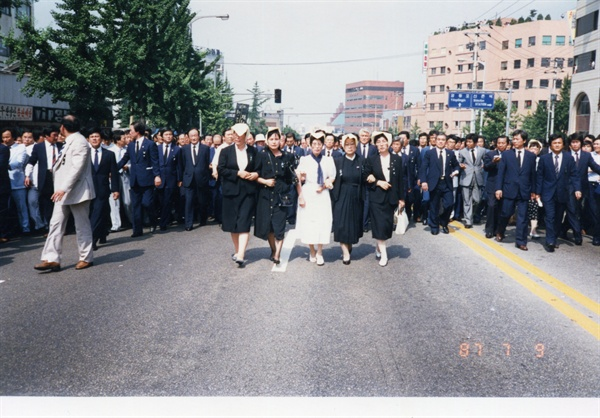 이희호 여사 생애사진 100선 1987년 이한일 열사 장례식 날 거리행진 중인 이희호 여사. 이태영 선생과 함께 걸었다. (가운데 흰옷이 이희호)