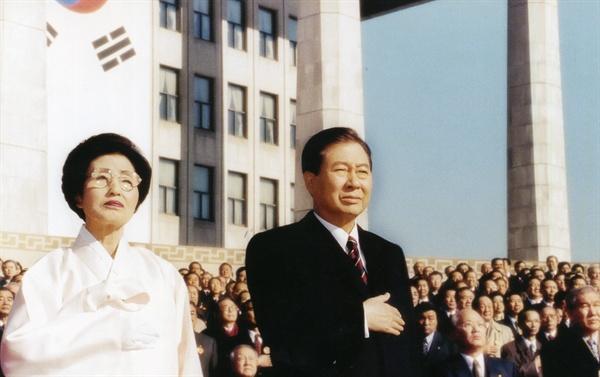이희호 여사 생애사진 100선 김대중 대통령과 이희호 여사가 1998년 15대 대통령 취임식에서 국기에 대한 경례를 하고 있다.