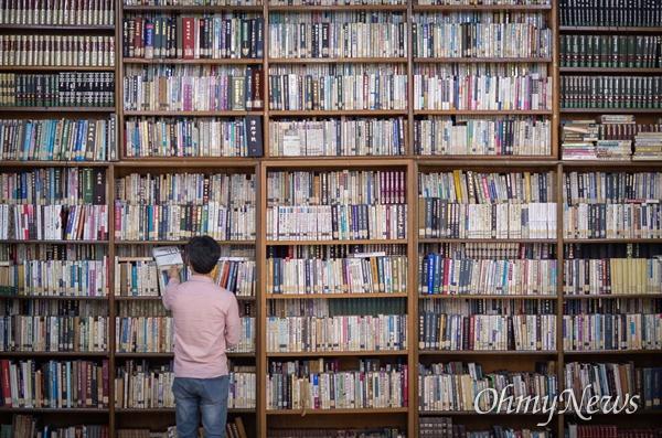 책마을 해리 이대건 대표의 키보다 훨씬 높은 책장에 책들이 가득 들어차 있다.