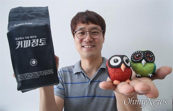 임병걸 대표가 커피 점토로 만든 커피큐브의 마스코트 '씨울이(C-Owl)'를 자랑하고 있다.