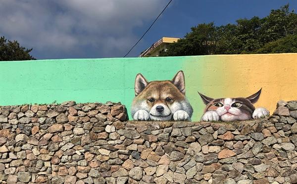 친근한 얼굴로 여행객을 맞이하는 마을벽화 속 강아지와 고양이.