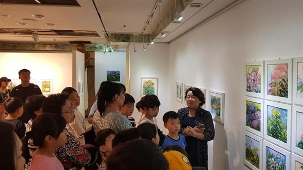 꽃 그림에 대해 이날 계룡문고 책방 나들이에 나선 논산 부창초등학교 가족들에게 설명하고 있는 전은복 화가