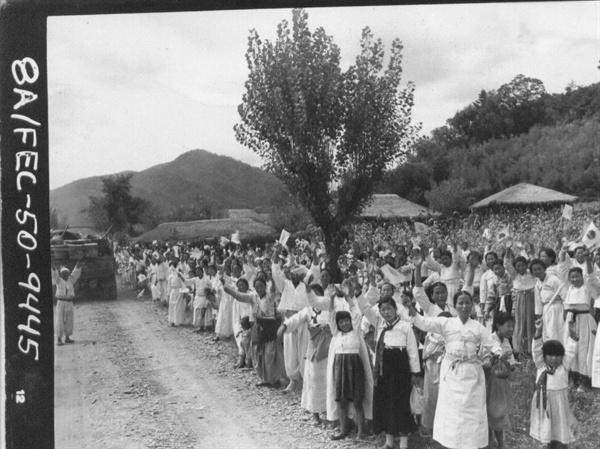 1950. 9. 27. 진주하는 군인에 따라 각기 다른 깃발을 들고 환영하는 흰옷입은 불쌍한 백성들.