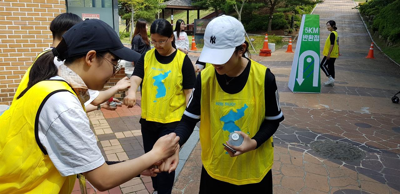 5km 반환점에서 확인 도장을 찍는 장면 학생회 임원들이 학생들에게 2019학생회 슬로건인 '함께가요 분솔' 도장을 찍는 장면